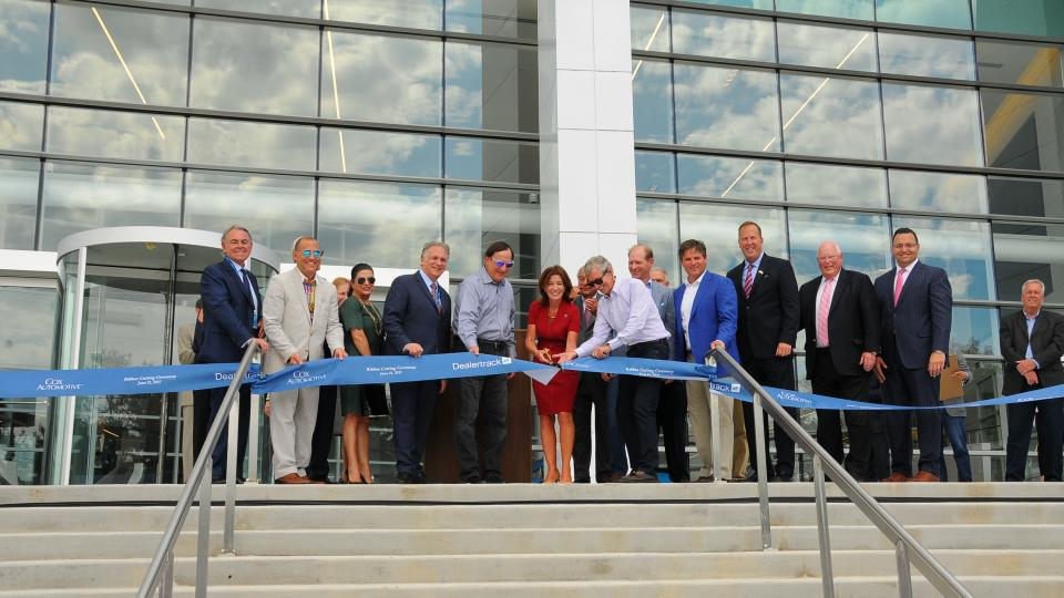 Ribbon cutting ceremony with group of people